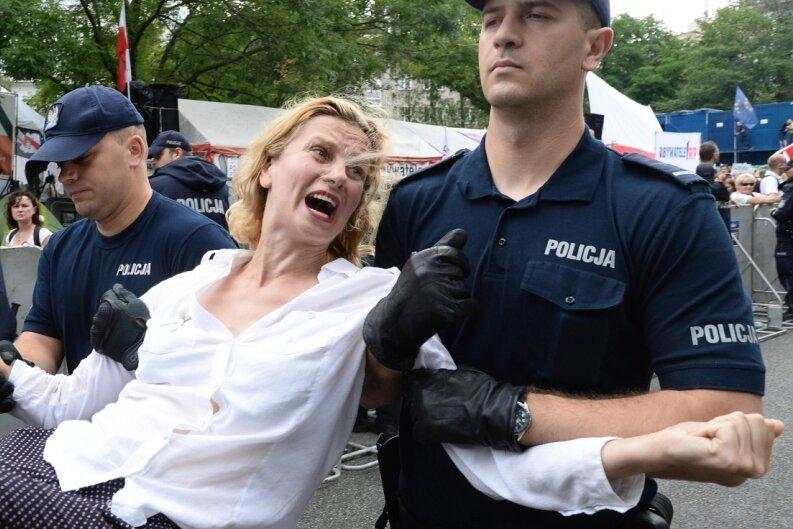 Polizisten tragen vor dem Parlamentsgebäude in Warschau eine Demonstrantin fort. Polens Regierung treibt ihre umstrittene Justizreform trotz Sanktionsdrohungen der EU-Kommission voran.