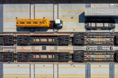 Sattelauflieger kommen am Terminal an. Dort werden sie von der Zugmaschine getrennt und auf die auf den Schienen bereitgestellten Konstruktionen gehoben. Auf den Waggons geht es dann umweltfreundlich durch Europa.