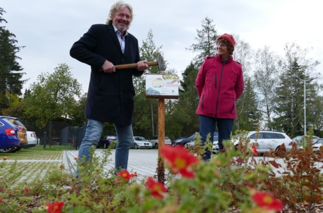 Auf dem von Grünflächen gesäumten Parkplatz bringen Flexiva-Geschäftsführer Rainer Hollnagel und Yvonne Scholz vom Landschaftspflegeverband ein Schild an, das den Nutzen der Lebensinseln erläutert.