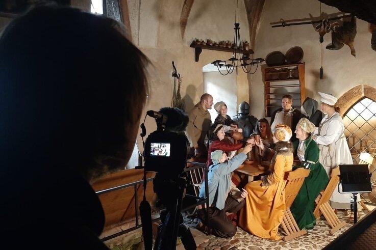 Auf einen Umtrunk in der Schlossküche. Jugendliche und Mitarbeiter des Rochlitzer Jugendladens stellen eine Szene aus ihrem Geschichtsprojekt nach.