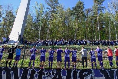 Die Auer Spieler feiern nach dem Spiel mit Fans, die sich außerhalb des Stadions im Wald versammelt haben.