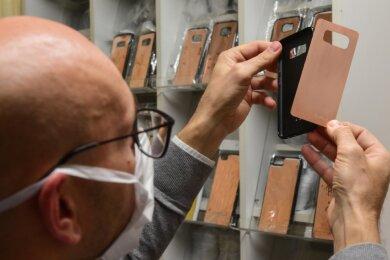 Der Hartmannsdorfer Thomas Austel zeigt, wie seine Handyhülle funktioniert: Auf einer Kunststoffschale wird eine Metallplatte aus Kupfer oder Messing aufgesetzt. Diese Legierungen haben antibakterielle und antivirale Eigenschaften, verspricht der Erfinder.