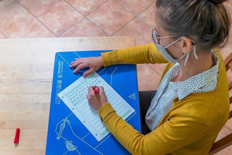 Erst wenige Buchstaben, dann kurze Wörter: Juliane Remenyi aus Dresden lernt das Schreiben noch mal neu.