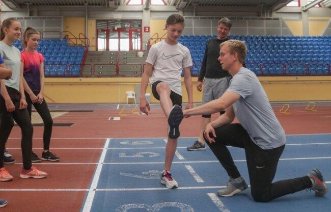 So wird es gemacht: Stützpunkttrainer Christopher Montague (r.) erklärt und zeigt detailliert, worauf es bei der Sprinttechnik ankommt. Im Hintergrund Uwe Bellmann, der Trainer der TSG Oederan.