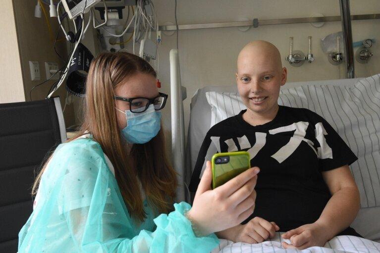 Sie lacht gern und freut sich über jede Nachricht von zu Hause: Nora Bürgel (rechts) liest mit ihrer Schwester Madlen im Chemnitzer KüchwaldklinikumNachrichten auf dem Handy.