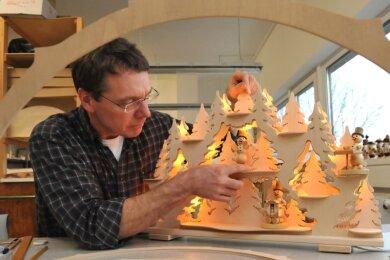 """<p class=""""artikelinhalt"""">Steffen Lubojanski produziert in seiner Werkstatt in Neukirchen erzgebirgische Holzkunst von Schwibbögen bis Pyramiden. """"Die Bäume wachsen nicht in den Himmel, aber es ist in Ordnung"""", sagt er über die Lage im Moment. Der Export spielt für ihn kaum eine Rolle. Also präsentiert er seine Produkte lieber vor der Haustür.</p>"""