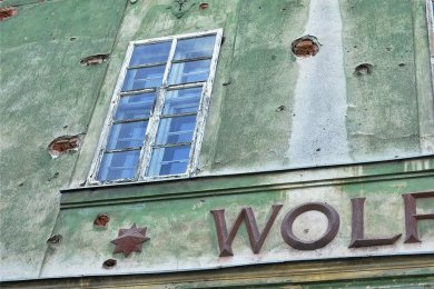 Einschusslöcher aus dem Zweiten Weltkrieg sind an der Fassade der früheren Gaststätte noch sichtbar.