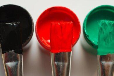 Pinsel mit den Farben in Schwarz, Rot und Grün.