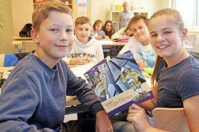 Die Sechstklässler Cody (v. l.), Max, Felix und Lena arbeiten mit dem Kinder-Orgelführer, der vor acht Jahren an ihrer Schule entstanden ist.