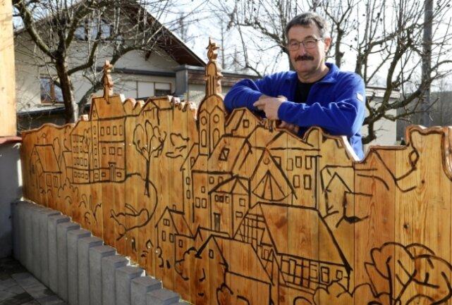 Peter Schnabel an seinem kunstvollen Grundstückszaun.