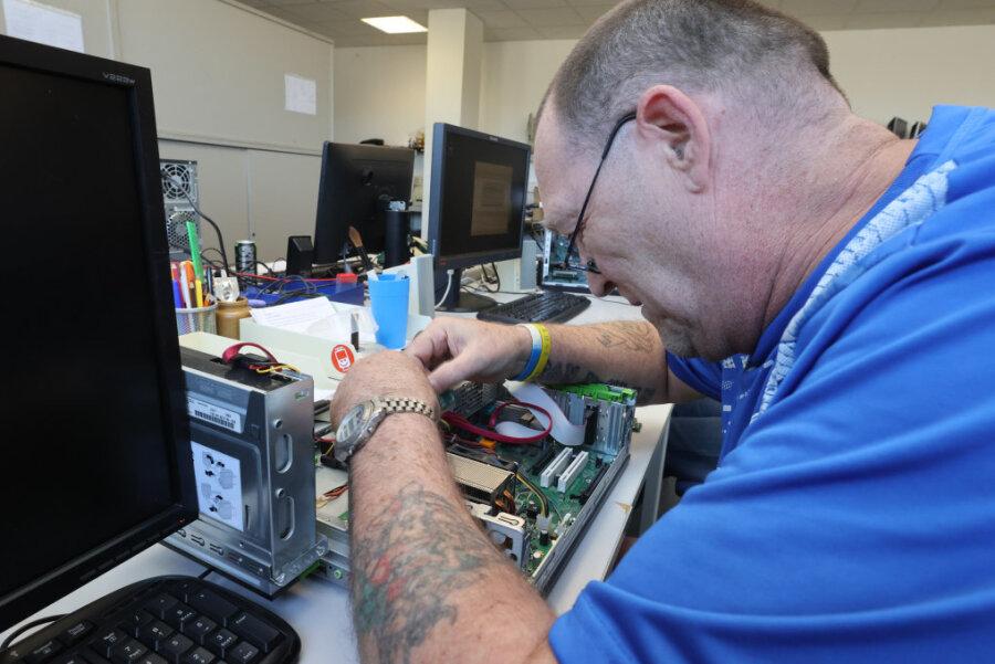 Rolf Schmidt arbeitet in Weimar an einem reparaturbedürftigen Computer.
