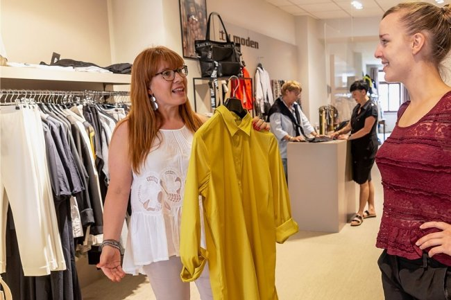 Seit Freitag kann man wieder ohne Maske einkaufen - auch bei Betty Moden in Annaberg. Verkäuferin Grit Lang (l.) spricht mit Kundin Helene Schröer.