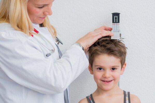 Bei der Untersuchung vor Schulbeginn wird auch die Körpergröße der Kinder gemessen - wie auf diesem Symbolbild. Familien aus dem gesamten Landkreis müssen für die Tests nach Zwickau kommen.