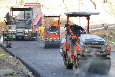 Mithilfe von Dampfwalzen wird der neue Straßenbelag auf der Mogatec-Zufahrt in Grießbach befestigt.
