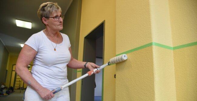 Malermeisterin Kerstin Weißflog von der Malerfirma Adrett-Design aus Zwickau streicht die Wände in der erstenEtage des Julius-Mosen-Gymnasiums Oelsnitz in einem freundlichen Gelb-Ton.