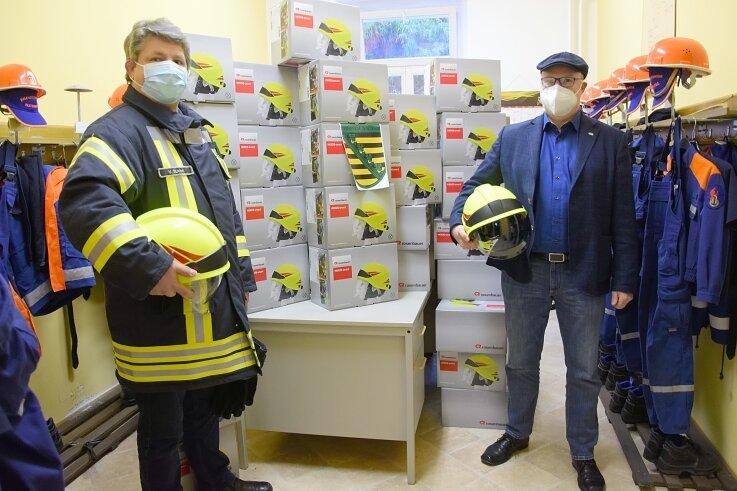 Stadtwehrleiter Volker Strobel (links) und Bürgermeister Sandro Bauroth bei der Übergabe der neuen Feuerwehrhelme in Elsterberg.