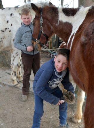 Das gehört dazu: Kathleen Rudas Sohn Tom (vorn) und Erik Schubert, der regelmäßig zum Reiten kommt, mit Pferd Chai bei der Hufpflege.