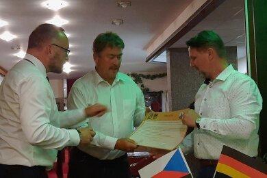 Reumtengrüns Ortsvorsteher Uwe Ebert (Mitte) und Svobodas Bürgermeister Petr Tyfa (rechts) mit dem Vertrag. Mit im Bild: Dr. Jens Baumann (Beauftragter für Vertriebene und Spätaussiedler in Sachsen).