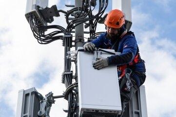 Ein Techniker installiert eine Antenne für das 5G-Funknetz auf einem Hausdach.