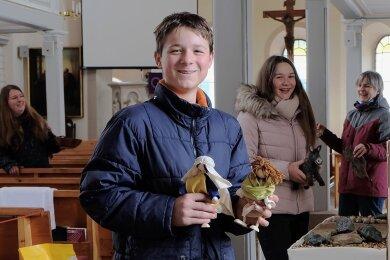 Kreativität in der Pandemie: In der Oelsnitzer Christuskirche wird in sechs Szenen die Passionsgeschichte dargestellt. Vorbereitet wird sie unter anderem von Clemens und Helena Teichmann (vorn).