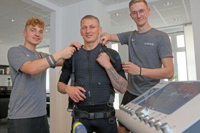 André Herold (l.) und Likas Dörken (r.) rüsten Marc-Philipp Zimmermann mit der EMS-Technik aus.