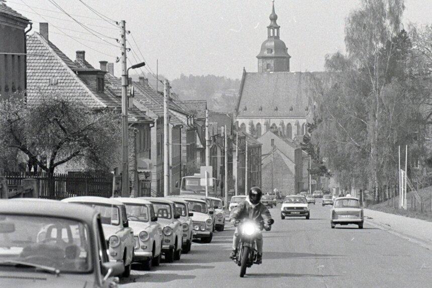 Nach der Wende und der Einheit beider deutscher Staaten gab es für die politischen Entscheidungsträger in Penig viel anzupacken. Es musste in den Folgejahren in die Infrastruktur genauso investiert werden wie in die Bausubstanz. Im April 1991 prägten sowohl Freileitungen das Bild der Chemnitzer Straße, als auch die dort geparkten Trabis. Ein VW Golf zeigt jedoch, dass eine neue Zeit angebrochen war.