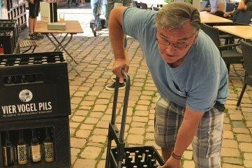 Siegfried Eichler lädt sich zwei Kisten Craft-Beer auf seinen Handkarren. Damit spendete er zugleich 20Euro für den CFC.Foto: Michael Brandenburg