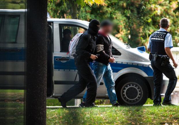"""Mutmaßliche Rechtsterroristen, die am Morgen in Bayern und Sachsen festgenommen wurden, erreichen den Bundesgerichtshof und werden von Polizisten abgeführt. Die sieben festgenommenen Deutschen sind den Angaben zufolge unter anderem dringend verdächtig, gemeinsam mit dem 31-jährigen Christian K. eine rechtsterroristische Vereinigung namens """"Revolution Chemnitz"""" gegründet zu haben."""