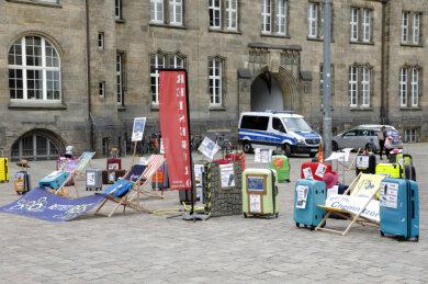 Auf dem Neumarkt demonstrieren Reisebüro mit leeren Koffern.