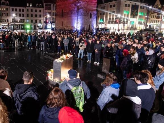 Trauernde stehen vor dem Roten Turm auf dem Marktplatz in Halle