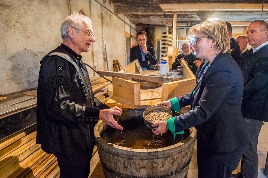 Im Wäschehaus der Fundgrube Wolfgangmaßen in Schneeberg erklärte Vereinsvorsitzender Volkmar Müller Ministerin Barbara Klepsch, wie früher das Erz gewaschen wurde. Die Vorrichtungen in diesem Gebäudeteil haben die Vereinsmitglieder alle selbst nach historischem Vorbild gebaut.