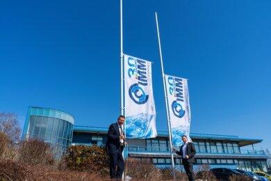 Professor Detlev Müller (l.) und René In der Stroth hissen eine Fahne anlässlich des 30-jährigen Bestehens von IMM.