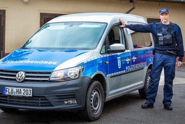 Thomas Karl mit seinem Dienstfahrzeug, einem VW Caddy, der mit Spezialfolie ein polizeiähnliches Design verpasst bekommen hat.