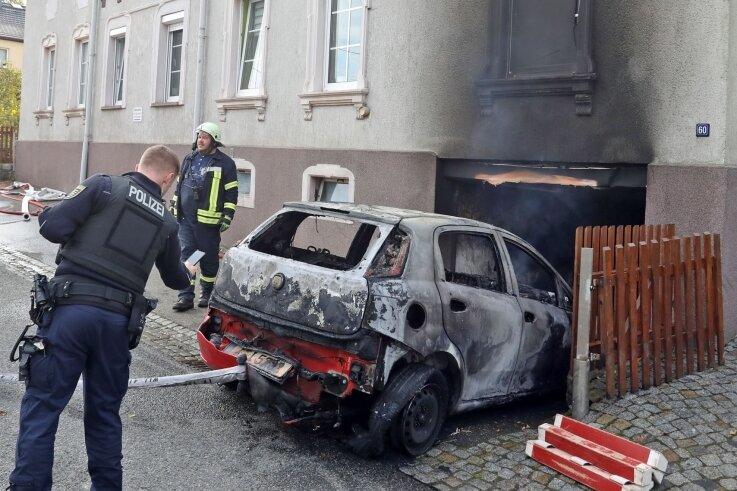 Einsatzkräfte der Feuerwehr ziehen das völlig ausgebrannte Autowrack aus der Garage des Hauses.