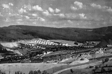 """Für westliche Geheimdienste von höchstem Interesse: das Objekt 98 (Mitte) in Johanngeorgenstadt. In dieser """"Erzfabrik"""" wurde Uranerz in Mahlwerken zerkleinert, mit Wasser und Chemikalien versetzt und immer wieder durchgeschüttelt, wodurch sich das Uran absetzte. Dieses Konzentrat wurde in die Sowjetunion geliefert. Die Erzwäsche war terrassenförmig angelegt, damit das Material leichter von Station zu Station transportiert werden konnte. Am Hang gegenüber: die eigens für Bergleute errichteten Wohnbaracken des heutigen Ortsteiles Pachthaus."""