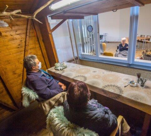 Maria Drummer (vorne r.) und Christian Arnold (l.) besuchen Gudrun Roscher (hinterm Fenster). Die Weihnachtsmarktbude wurde von der Stadtverwaltung zur Verfügung gestellt.
