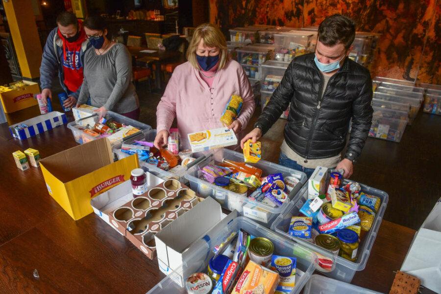 """Ein Team der Chemnitzer Tafel (von links Rafael Kraft, Anja Rahn, Christiane Fiedler) sortieren mit Tommy Seidel (rechts) vom Café Michaelis die Spenden des """"verkehrten Adventskalenders""""."""