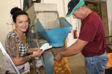 Susann Hofmann und Piotr Maciejewski sacken die Kartoffeln in Zehn-Kilo-Säcken ab.