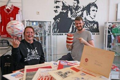 Kathrin Maneke und Chris Scheundel beim Aufbau der Ausstellung im FSV-Fanshop. Der Vereinsvorsitzende zeigt die Rassel von Kurt Mehlhorn.
