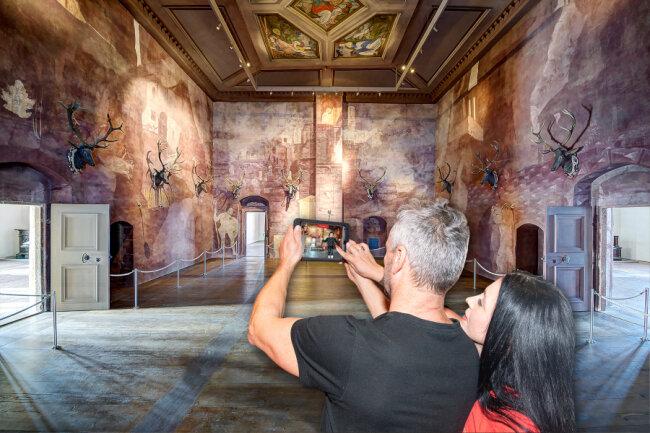 Mit dem EntdeckerPad erkunden Besucher den Venussaal in Schloss Augustusburg virtuell.