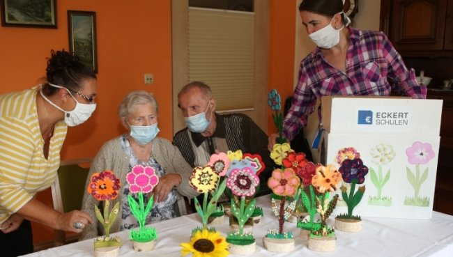 Heike Weidauer (links) und Daniela Sens von den Eckert-Schulen haben diese Woche mit den Holzblumen Mitarbeiter und Bewohner der Seniorenresidenz Edelweiß in Schwarzenberg überrascht. Hannelore und Hans Pausch freuten sich über die unvergänglichen Kunstwerke.