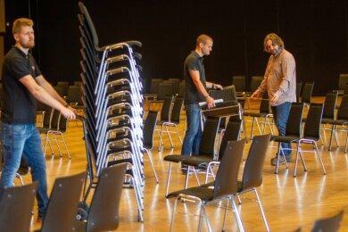 Alexander Poppitz, Marc Rost und Ronny Bley. Sie passen die Festhalle den Corona-Auflagen an, indem sie Stühle aus dem Saal tragen.