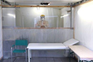 Hier in der Garage behandelt Christoph Lohmann Patienten mit Covid-Symptomen. Zwischen ihnen und dem Arzt befindet sich eine Trennwand mit Plexiglas im oberen Bereich und einem PVC-Lamellenvorhang.