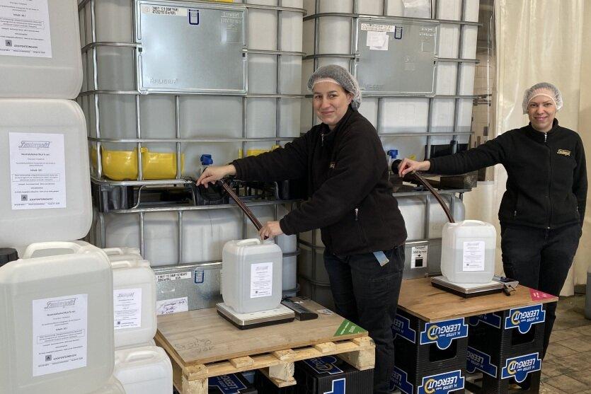 Die Produktionsmitarbeiterinnen Doreen Schmidt (l.) und Anja Link von der Lautergold Paul Schubert GmbH in Lauter füllen den hochprozentigen Alkohol in Plastekanister ab. Statt Spirituosen stellt das Unternehmen nun ein eigenes Handdesinfektionsmittel her.