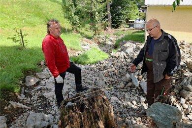 Michael Buntin (rechts) und Uwe Groh stehen inmitten der angespülten Sedimente. Nicht nur in diesem Bereich hat sich das Bett vom Ruderitzbach nach dem Starkregenereignis verändert. Beide hoffen nun auf Hilfe vom Bauhof.