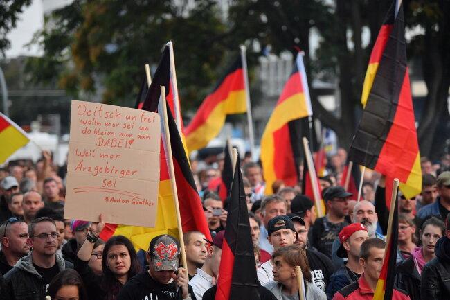 Demonstration des rechtspopulistischen Bündnisses Pro Chemnitz: Mit Deutschland-Fahnen stehen Teilnehmer bei der Demo.