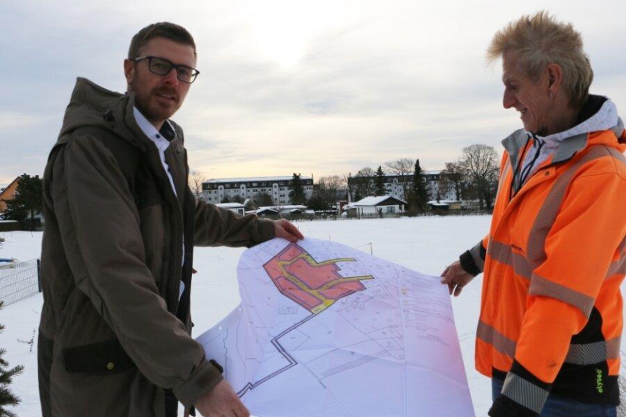 Oberhalb von Syrau können voraussichtlich schon dieses Jahr Eigenheime gebaut werden. Bürgermeister Michael Frisch (links) und Luz Woratsch von der Bauverwaltung der Gemeinde zeigen, wo das neue Wohngebiet Lerchenberg geplant ist. Im Hintergrund sieht man die Syrauer Wohnblöcke.