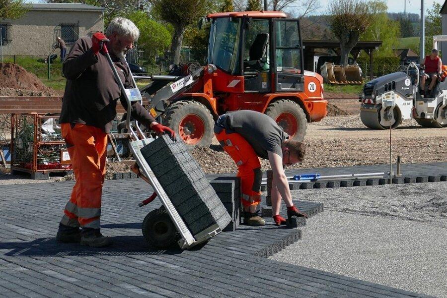 Während die Kollegen die Fläche für den Bolzplatz einebnen, pflastern Andreas Seidel (links) und Nick Schubert den Festplatz.