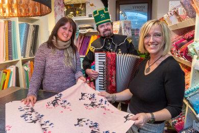 Der Einkauf von Bianca Oertel (l.) im Stoffladen von Annett Voigt (r.) wurde von Thomas Haubold, der in Bergmannstracht Akkordeon spielte, musikalisch umrahmt.