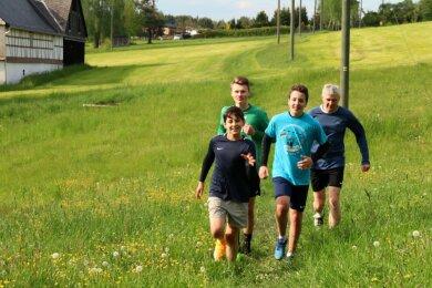 Von vorn: Richard (15), Björn (14), Edgar (16) und Vereinsvorsitzender Rigo Völkel auf der Waldkirchener Waldlauf-Strecke.